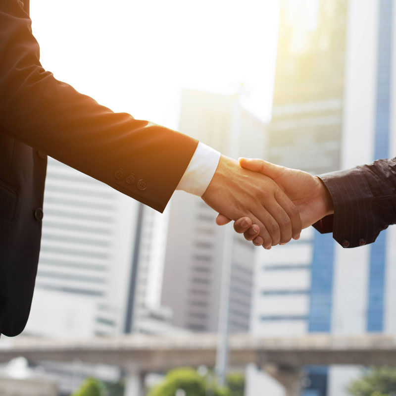 Experienced commercial real estate professionals shake hands on deal
