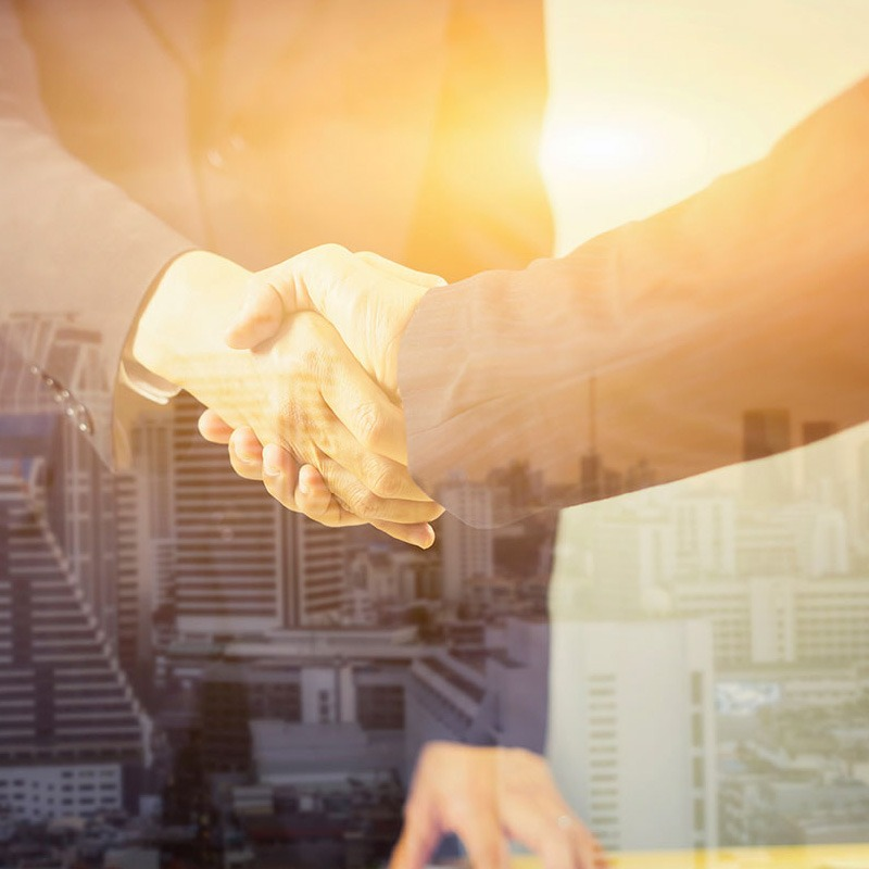 Catalyst Capital partners in suits handshake with real estate buildings in background