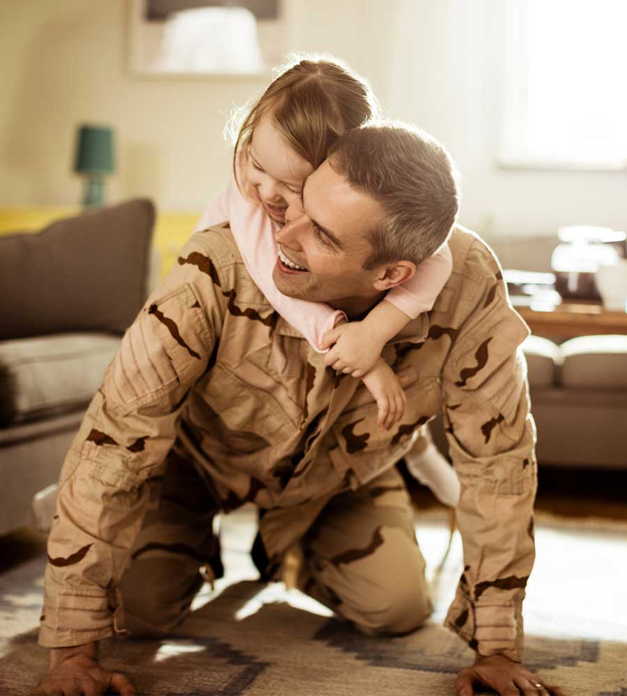 Photo of American soldier playing with his daughter at home
